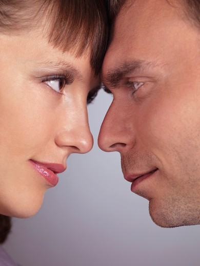 Closeup portrait of a man and a woman touching foreheads and looking at each other : Stock Photo