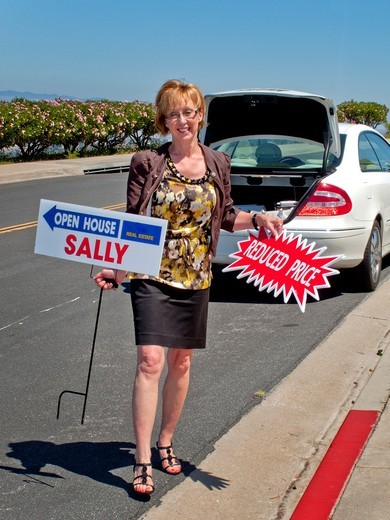 A woman realtor posts temporary signs pointing the way to her ´open house´ exhibition in Laguna Niguel, CA, and offering a reduced price for the property : Stock Photo