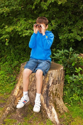 Stock Photo: 1566-867377 An eleven year old boy birdwatching with binoculars at Fairhaven woodland and water garden in South Walsham , Norfolk , England , Britain , Uk