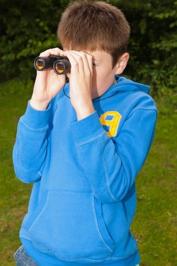 An eleven year old boy birdwatching with binoculars at Fairhaven woodland and water garden in South Walsham , Norfolk , England , Britain , Uk : Stock Photo