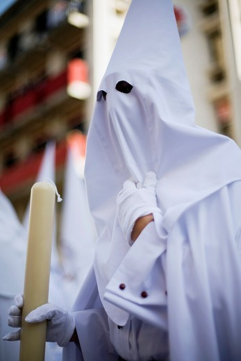 Hooded penitent bearing a candle, Palm Sunday, Seville, Spain : Stock Photo