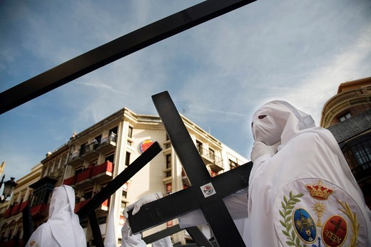Stock Photo: 1566-867889 Hooded penitents bearing wooden crosses, Palm Sunday, Seville, Spain