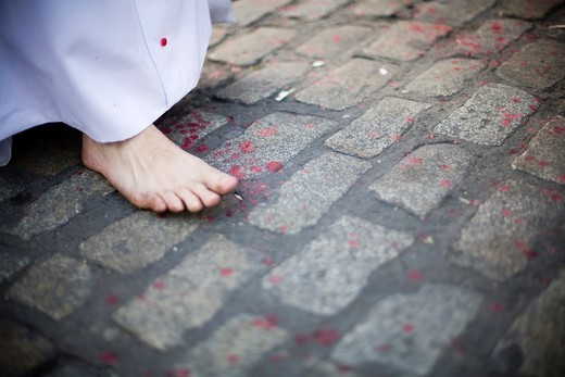 Detail of a barefoot penitent walking on the pavement with melted wax drops, Holy Week 2008, Seville, Spain : Stock Photo