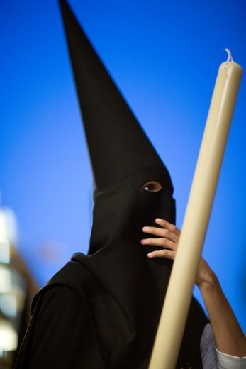 Stock Photo: 1566-867921 Hooded penitent against a dusk sky, Holy Week 2008, Seville, Spain