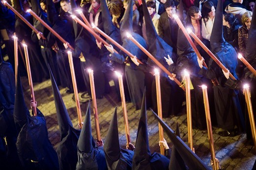Hooded penitents bearing candles on Good Friday, Seville, Spain : Stock Photo