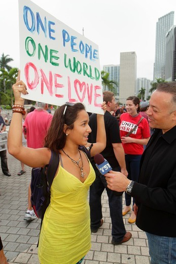 Florida, Miami, Biscayne Boulevard, Freedom Torch, Occupy Miami, demonstration, protest, protesters, anti Wall Street, banks, corporate greed, sign, poster, message, 99, holding, teen, girl, man, reporter, interview, microphone, TV, television, : Stock Photo