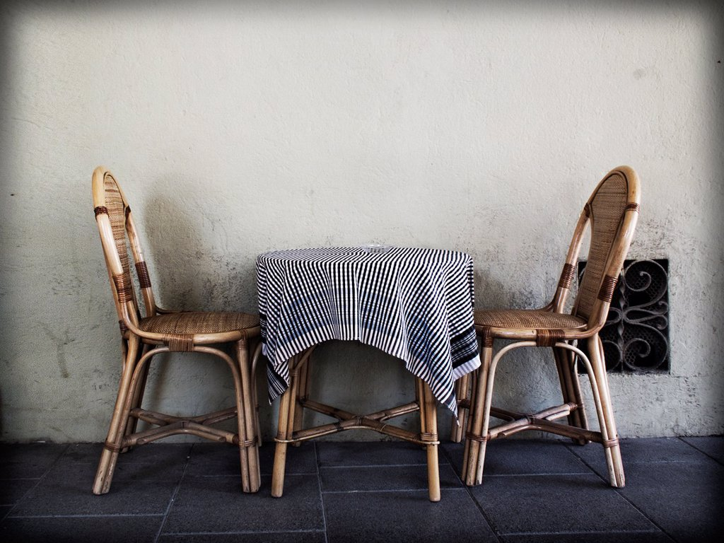 Stock Photo: 1566-873882 Two wicker chairs with a table and tablecloth on the terrace of a bar.