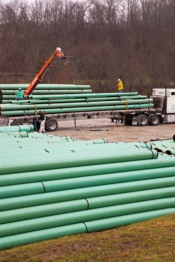 Washington, Pennsylvania - Workers load pipe for pipeline construction on a truck in southwestern Pennsylvania where hydraulic facturing is commonly used to increase gas recovery  Fracking is controversial because of environmental problems : Stock Photo