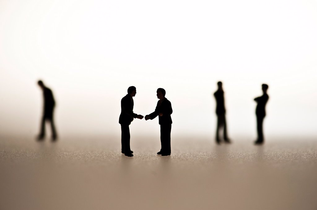 silhouetted small figures conceptual image for business men meeting : Stock Photo