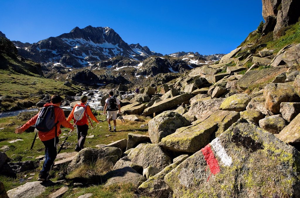 Stock Photo: 1566-881346 Trippers and Signposting of GR-11 in Circ de Colomers, near Obago lake,Aran Valley, Aigüestortes and Estany de Sant Maurici National Park,Pyrenees, Lleida province, Catalonia, Spain
