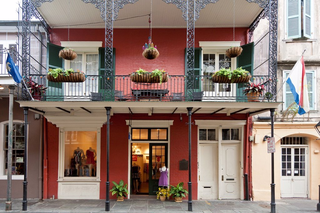 Stock Photo: 1566-881927 Upscale dress shop under balcony with decorative wrought iron railings in the French Quarter of New Orleans, LA