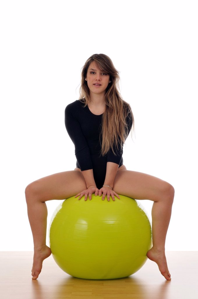 young woman doing exercise, gymnastics, with a large green ball, giant ball : Stock Photo