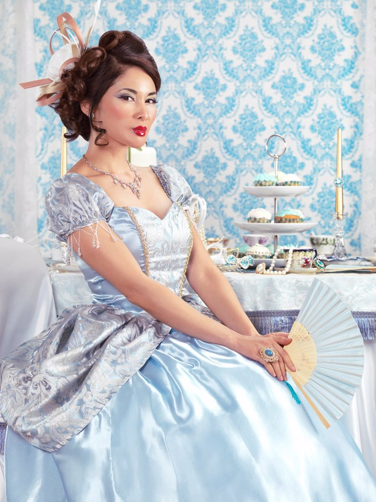Beautiful asian lady in a luxurious blue dress sitting at a tea party table with a fan : Stock Photo