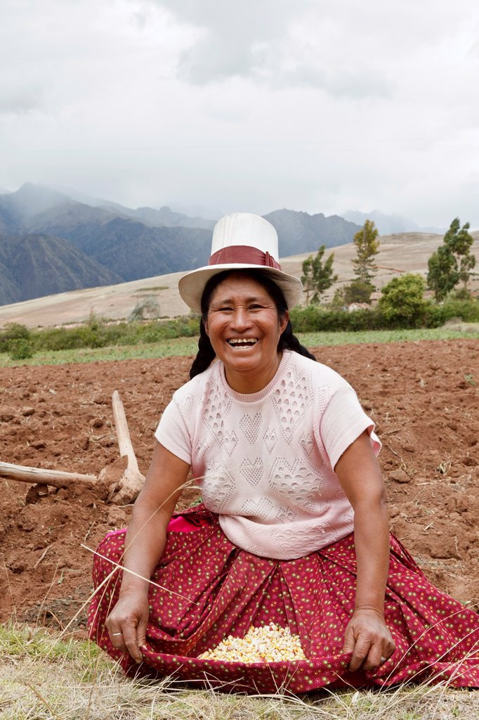 Stock Photo: 1566-885697 Peruvian Lady in a Top Hat,showing the corn that she was planting  Chinchero,Peru