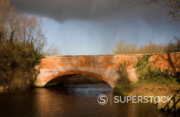 Stock Photo: 1566-888449 Red brick bridge crossing River Deben, Ufford with rain and storm clouds, Suffolk, England