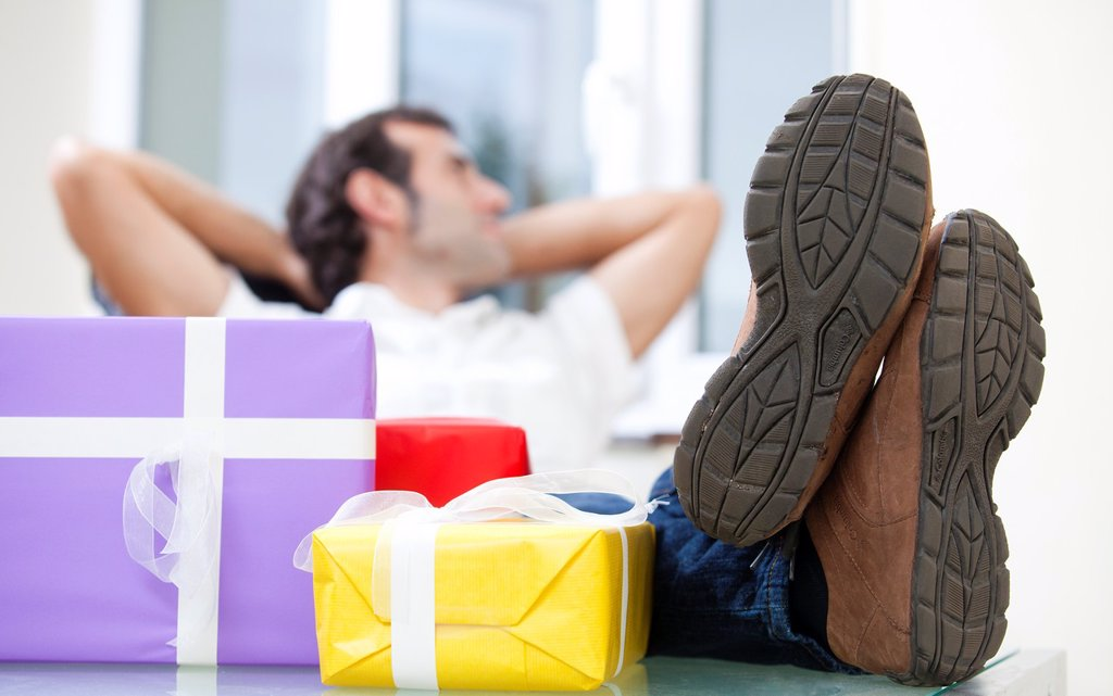 Stock Photo: 1566-891311 A man rests happily next to a pile of presents