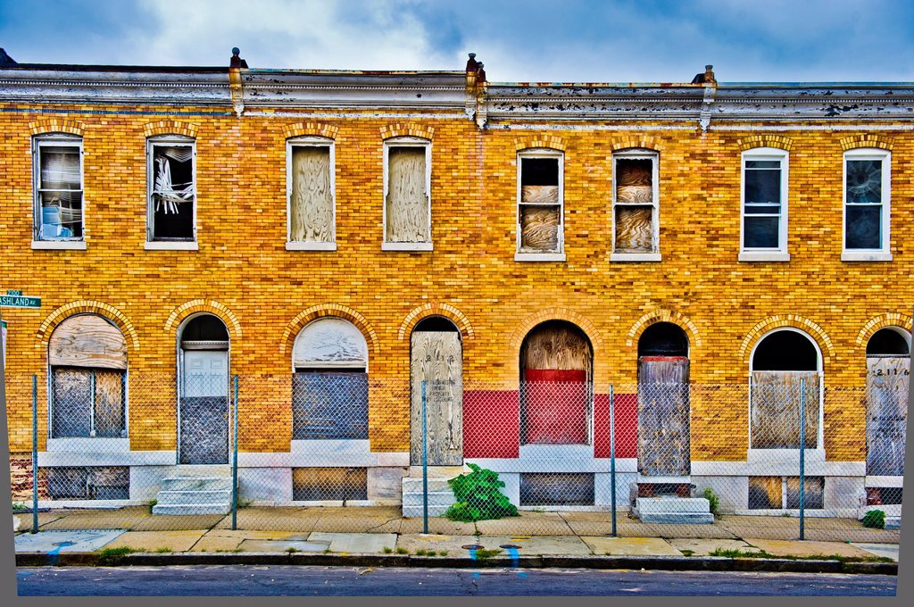Deserted row houses boarded up and gated off : Stock Photo