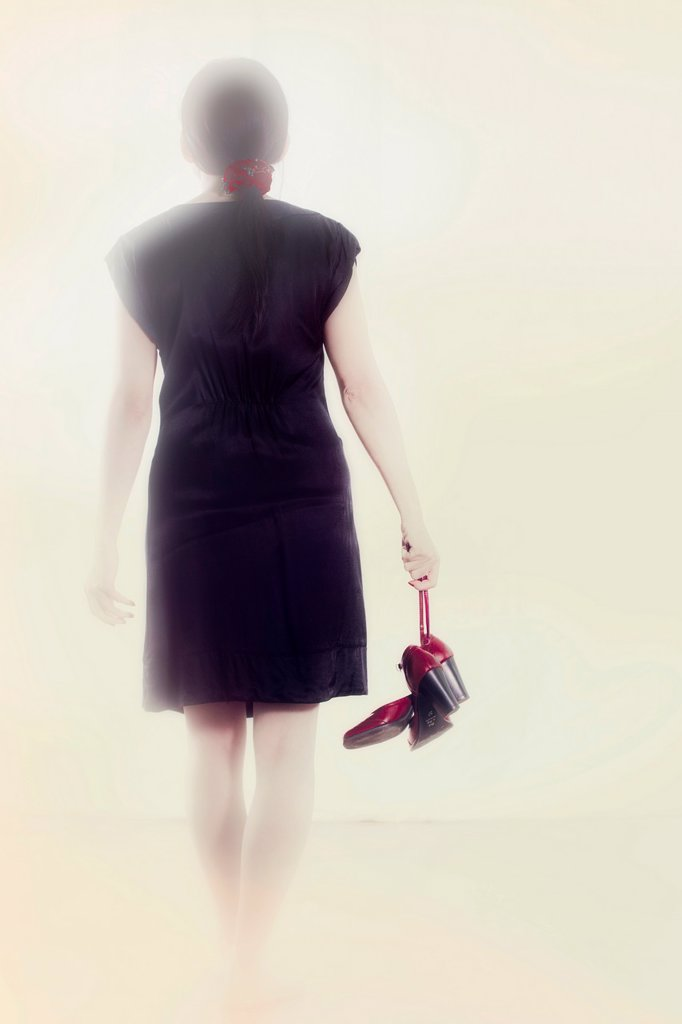 Stock Photo: 1566-892385 Woman in a black dress goes with red shoes in hand into the light