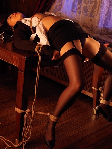 Stock Photo: 1566-894368 Sexy asian woman in black stockings tied with bondage ropes to a table