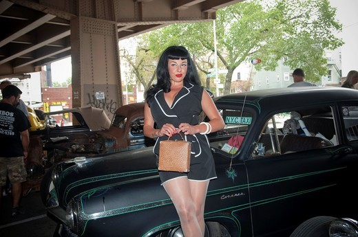 Young woman poses for photo at the ´Kustom Kills and Hot Rod Thrills´ car show under the Brooklyn-Queens Expressway in the Williamsburg neighborhood of New York : Stock Photo