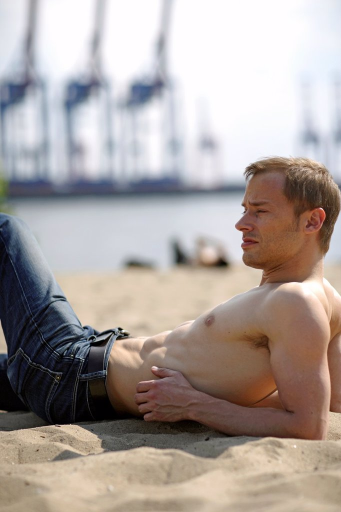 Halb body image of young caucasian man, seen from the side, Jeans and nacked, muscular body, turning his head to the side and looking into the far distance to infinity, laying on the beach of river Elbe with blurred people, water and cranes of the harbor. Halb body image of young caucasian man, seen from the side, Jeans and nacked, muscular body, turning his head to the side and looking into the far distance to infinity, laying on the beach of river Elbe with blurred people, water and cranes of  : Stock Photo