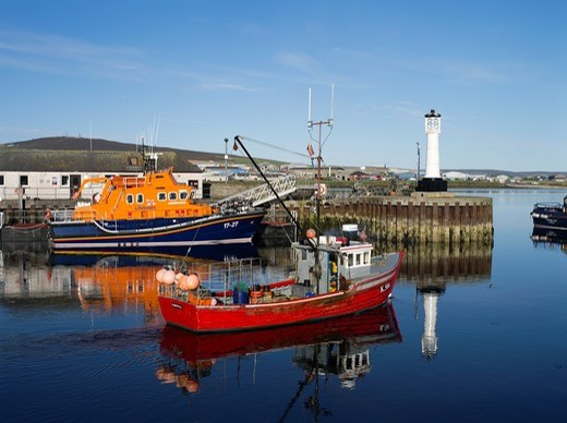 Stock Photo: 1566-899462 Kirkwall harbour KIRKWALL ORKNEY Red crab boat leaving harbour lifeboat RNLB Volunteer Spirit at quay