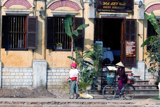 Conical hat woman on bicycle pedals past riverside restaurant Hoi An Vietnam : Stock Photo