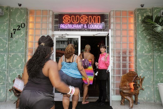 Stock Photo: 1566-899648 Florida, Miami Beach, Collins Avenue, Kung Fu Kitchen and & Sushi, restaurant, Catalina Hotel, front, entrance, neon sign, Black, women, entering, hostess,