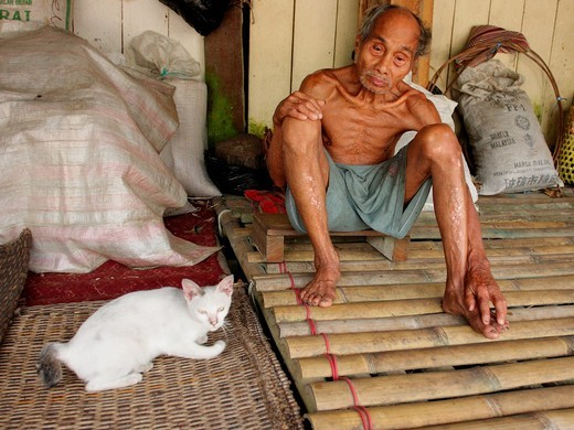 Malaysia, Sarawak, bidahyu man sitting inside long house. : Stock Photo