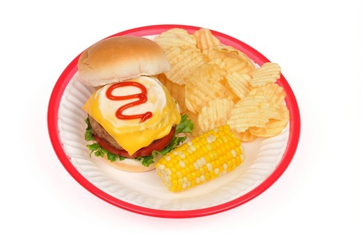Turkey burger with cheese,lettuce and tomato topped with mayonnaise and ketchup in bread roll with corn on the cob and potato chips on white paper plate in red retro plastic basket on white background cutout : Stock Photo