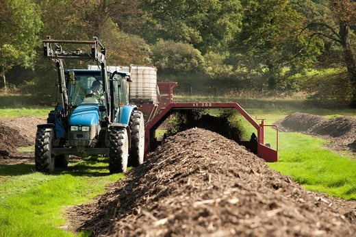 Composting domestic green household waste, UK - tractor turning over the material : Stock Photo