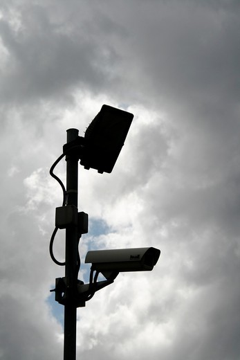 one cctv camera silhouette on high pole outdoors with dark moody sky : Stock Photo