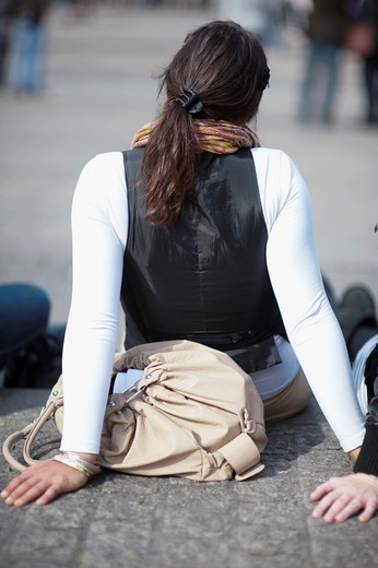 A young, female tourist is watching the events on de main square of Amsterdam: De Dam, while sitting down. : Stock Photo