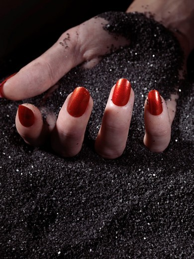 Woman´s hand with red nail polish lying on black sand : Stock Photo