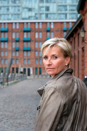 Blond haired executive woman, turning her head and looking back over her shoulder, seen from backside, with office building made of red bricks, windows and balconies in the background, Hamburg, Germany, Europe : Stock Photo