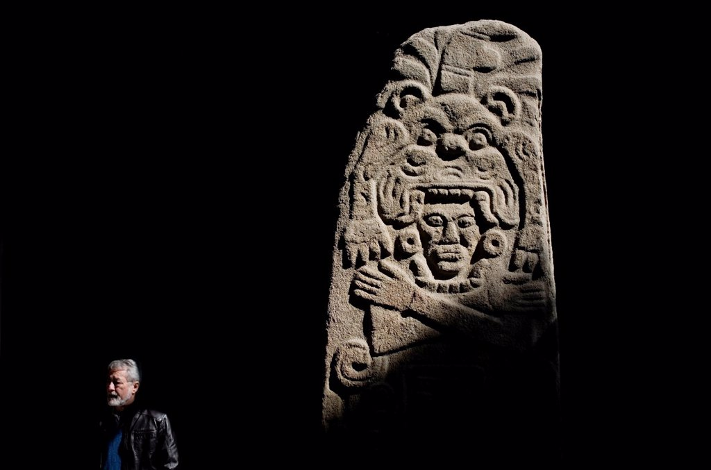 Stock Photo: 1566-902427 A mature man passes a stone stela displayed in the National Museum of Anthropology in Mexico City, December 1, 2011  The National Museum of Anthropology and History museumMuseo Nacional de Antropologia e Historia is located in the historic Chapultepec Par. A mature man passes a stone stela displayed in the National Museum of Anthropology in Mexico City, December 1, 2011  The National Museum of Anthropology and History museumMuseo Nacional de Antropologia e Historia is located in the historic Cha