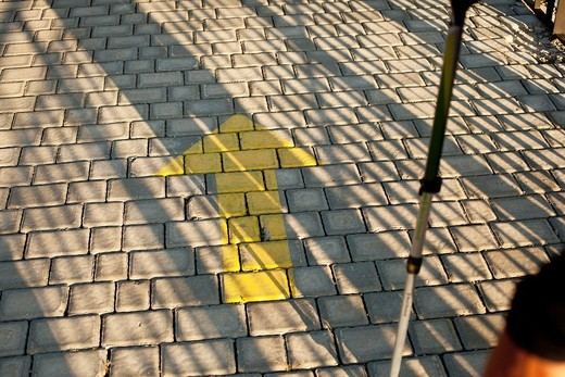 Yellow arrow marker pointing the way on the Camino de Santiago : Stock Photo