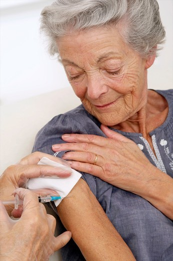Senior woman being vaccinated against the flue : Stock Photo