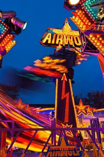 Speeding gondolas of the Airwolf thrill ride at night at the Freimarkt in Bremen, Germany, Europe : Stock Photo
