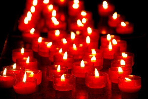 many lit candles in dark room in church : Stock Photo