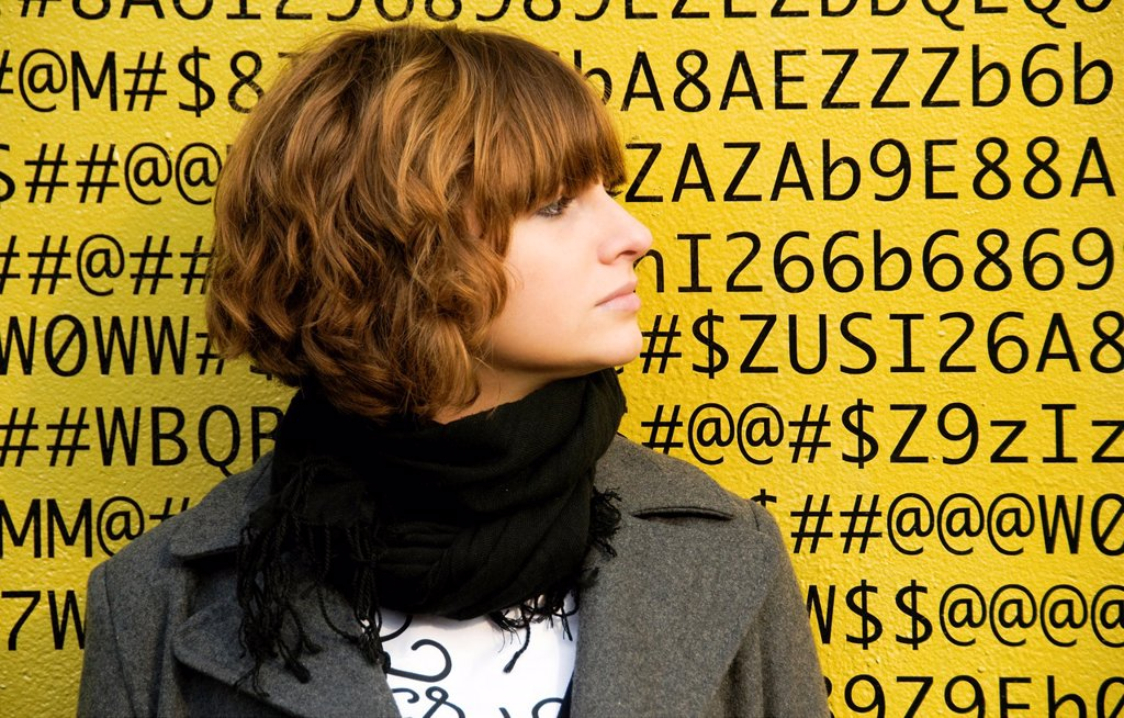 A face of young woman in front of numbers, letters, symbols, background is a painted wall of one of buildings in Geneva, Switzerland : Stock Photo