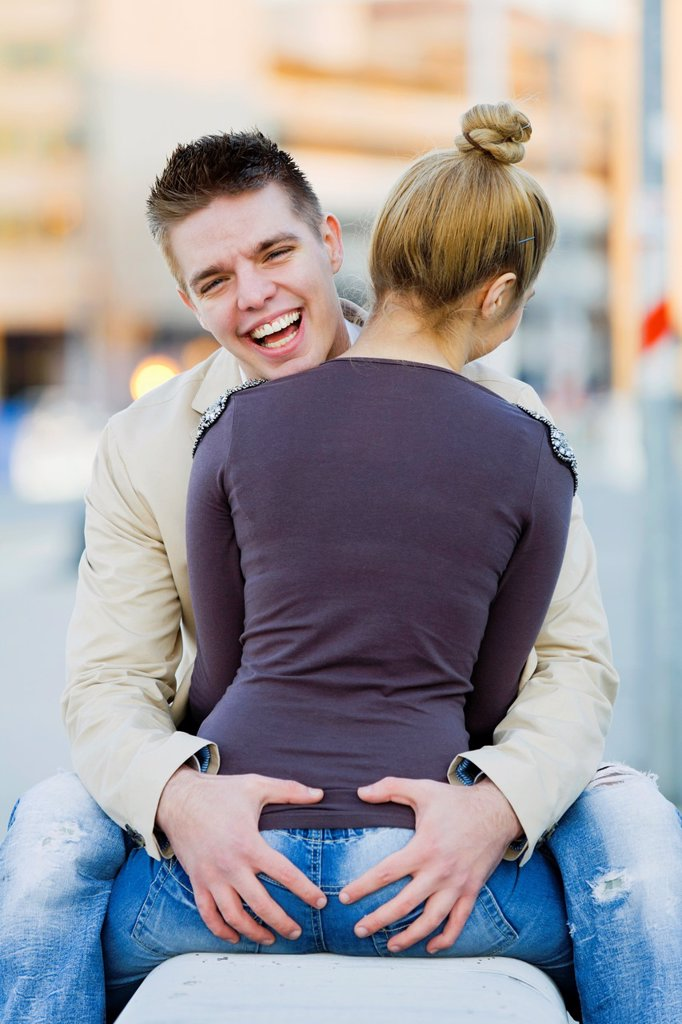 Intimate touch happy young couple on a bench : Stock Photo