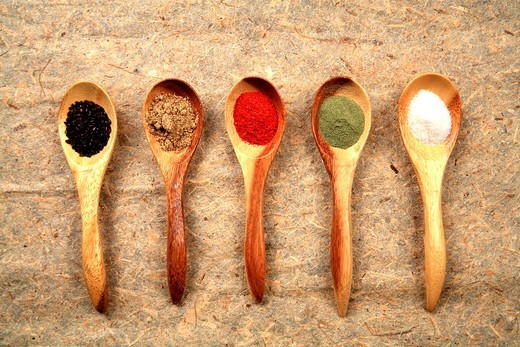 Assorted dried spices displayed on small wooden spoons : Stock Photo