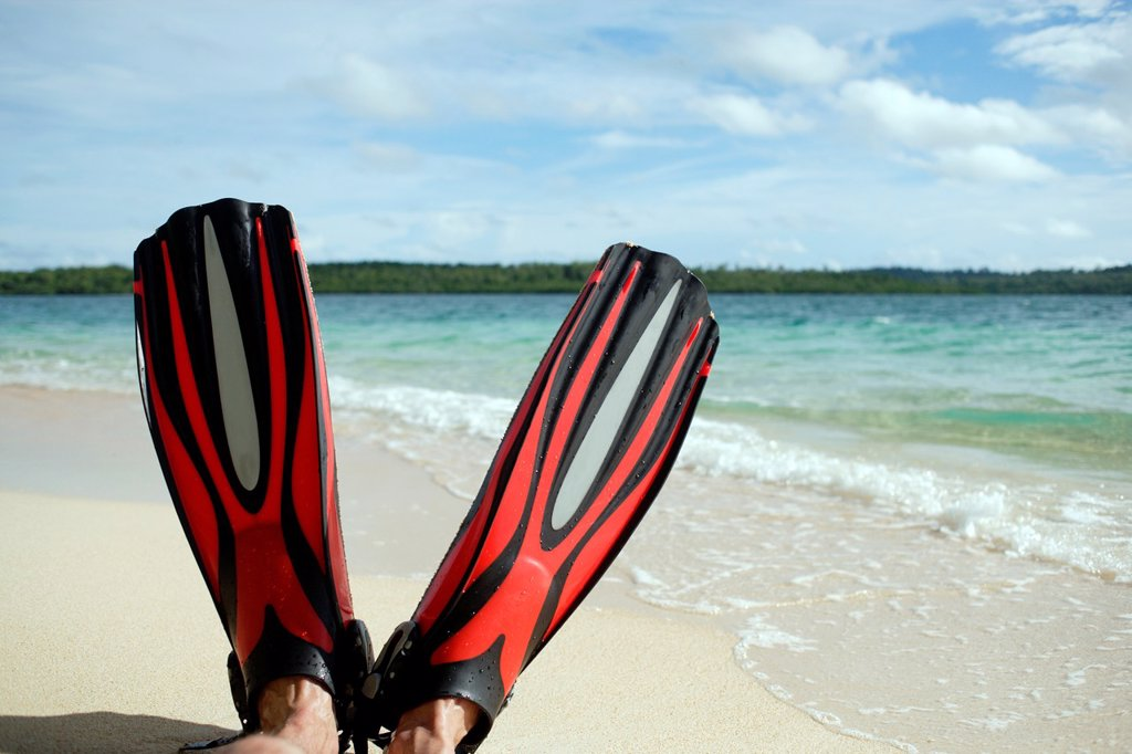 Stock Photo: 1566-910150 Close up of two red fins with male feet, holding up the fins at the beach with the turquise sea and blue sky with clouds in the background, sunny day, Papua Newguinea, Southeast Asia
