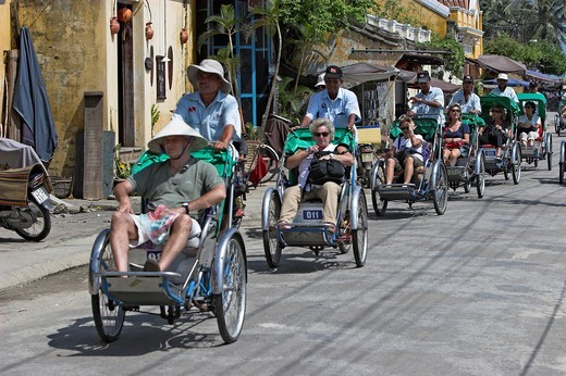 Stock Photo: 1566-910330 Visitors on group cyclo rickshaw tour of Hoi An historic town riverside mid Vietnam