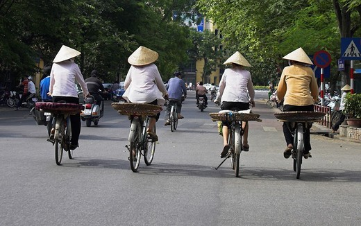 Thre women in conical hats on bicycles Hanoi Vietnam : Stock Photo