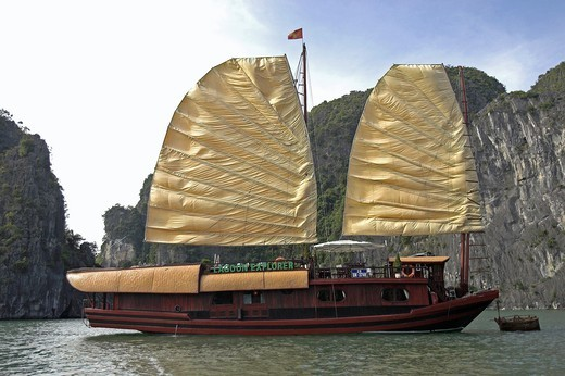 Large cruising junk with sails hoisted off rocky island Halong Bay Vietnam : Stock Photo