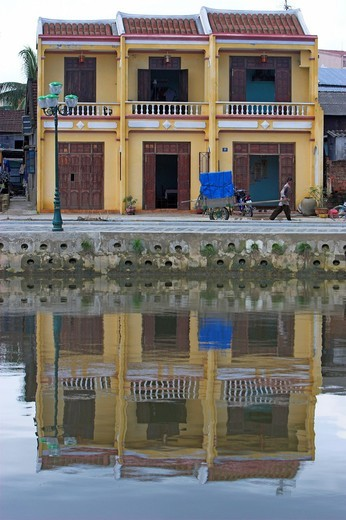 Man with hand cart and three pastel yellow terrace house reflected in river Hoi An historic town mid Vietnam : Stock Photo