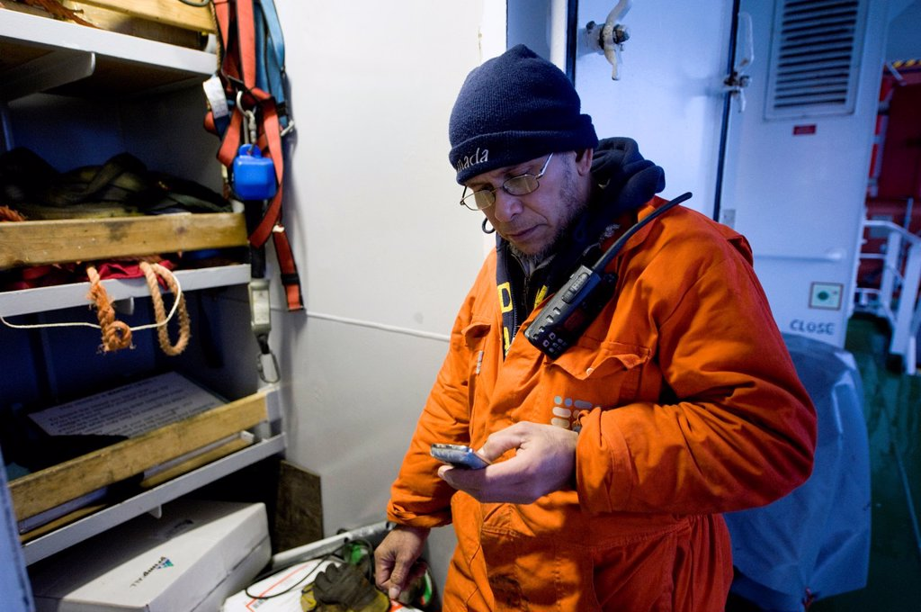 Stock Photo: 1566-912491 An Indonesian seaman or sailor on the container-vessel MV Flintercape, during a journey from Rotterdam, Netherlands, to Sundsvall, Sweden. The man is an ´Able Seaman´, who generally works on deck, and now checks is phone near the tools-room on the deck.