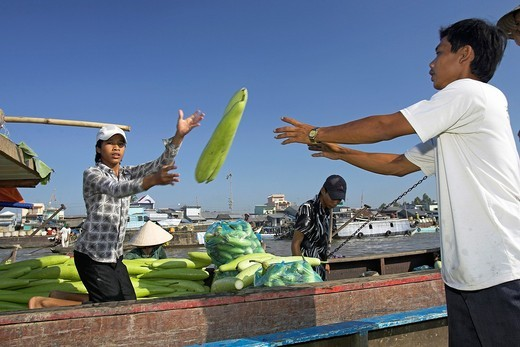Young man throwing winter melons boat to boat Cai Ran floating market near Can Tho Vietnam : Stock Photo